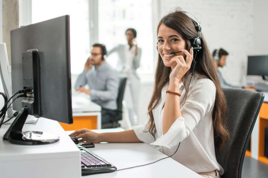 Young friendly operator woman agent with headsets working in a call centre. | Bild: 171044217