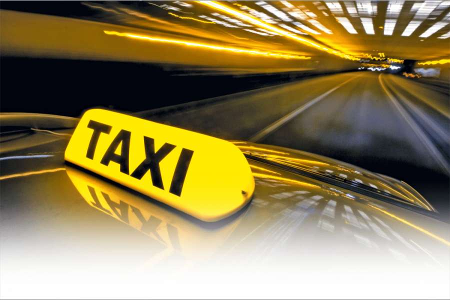 A cab at high speed on a motorway in an urban area with the lit taxi sign on top of its roof | Bild: Fotolia corepics